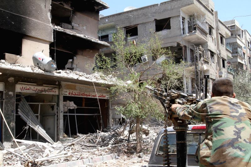 A Syrian soldier looks on at al-Mleiha town in the outskirts of Damascus, Syria, Aug. 15, 2014. Syrian government organized a trip to the town for journalists on ..