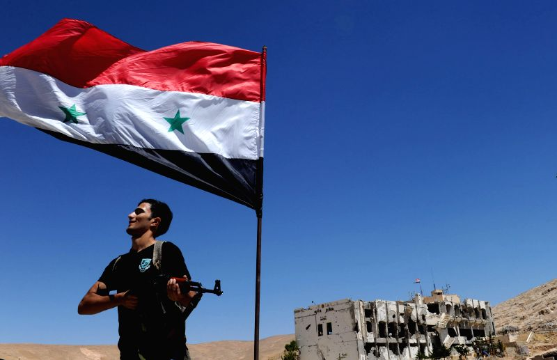 A man poses with a rifle under a Syrian national flag in the historic Christian town of Maaloula, north of Damascus, capital of Syria, Aug. 21, 2014. Maaloula is ..