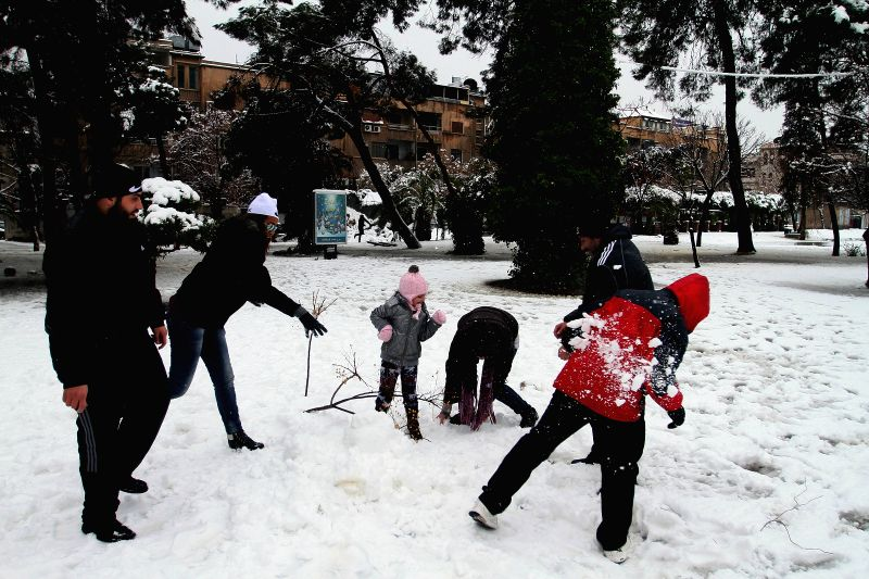 Syrians play with snow on a snow-covered street in Damascus, Syria, Jan. 7, 2015.