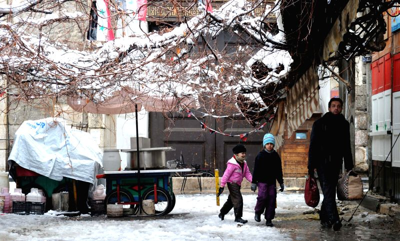 Children walk in the snow in Damascus, Syria, Jan. 7, 2015. Damascus saw this winter's first snowfall on Jan. 7, 2015.