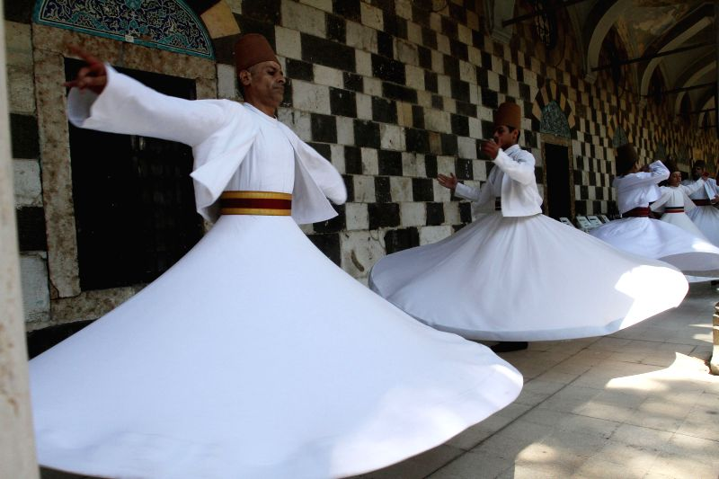 The whirling Dervishes perform as part of activities held at a bazaar for food and clothes organized under the auspices of the Syrian Tourism Ministry with lower ..