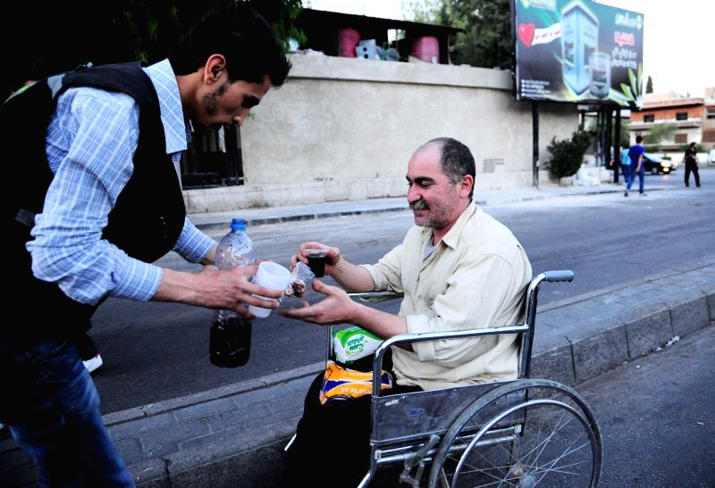 "DAMASCUS, June 6, 2017 - A volunteer distributes the Ramadan iftar meal to a passerby in Damascus, capital of Syria, on June 6, 2017. Volunteers invented something called the ""Ramadan ..."