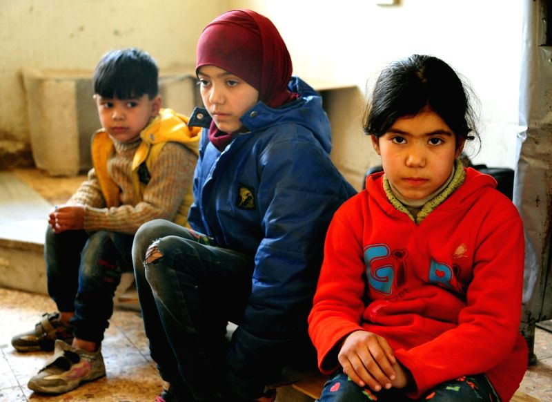 DAMASCUS, March 13, 2018 - Evacuated children sit in a temporary shelter in Wafidin area, northeast of Damascus, capital of Syria, on March 13, 2018. A total of 146 civilians on Tuesday left the ...