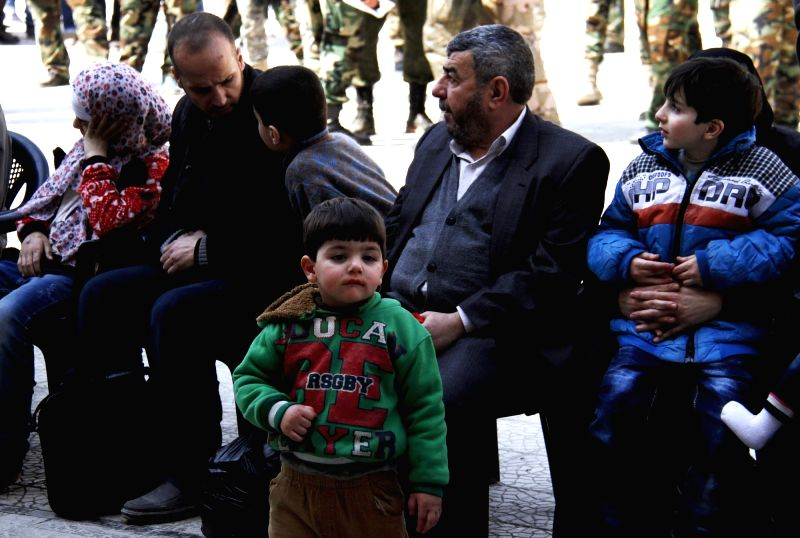 DAMASCUS, March 13, 2018 - Evacuated Syrian civilians wait at a temporary shelter in Wafidin area, northeast of Damascus, capital of Syria, on March 13, 2018. A total of 146 civilians on Tuesday left ...