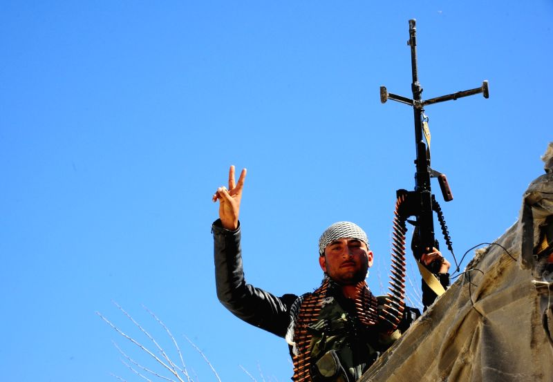 A Syrian soldier flashes the victory sign in a liberated area in the capital Damascus Eastern Ghouta countryside