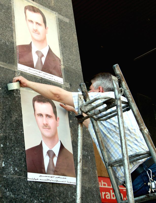 A worker puts up election posters in Damascus, Syria, May 12, 2014. A day earlier, the country's supreme constitutional court gave presidential candidates, Maher ...