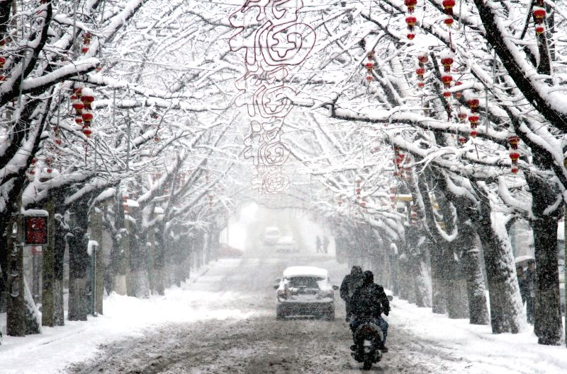 Local residents pass on a snow-blanketed road in Dandong, northeast China's Liaoning Province, Feb. 25, 2015. Dandong witnessed its first snowfall in the new Year ...