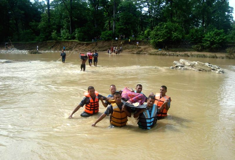 DANG, Aug. 26 2014 Policemen rescue a woman in flood in Dang, western Nepal, on Aug. 25, 2014. Around 150 people died and 270 others were missing in Nepal due to landslides and flooding ..