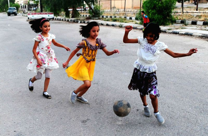 DARAA, July 10, 2018 - Three girls play football on the street in the capital city of Daraa province in southern Syria, on July 9, 2018. People remained in their homes until they were sure of a deal ...