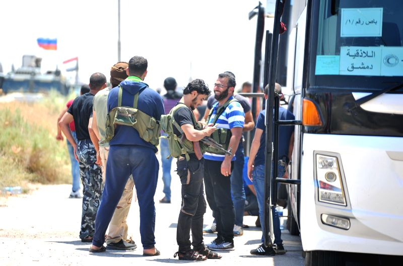 DARAA (SYRIA), July 16, 2018 People stand near a bus transporting the rebels and their families in the southern province of Daraa, Syria, on July 15, 2018. Rebels and their families ...
