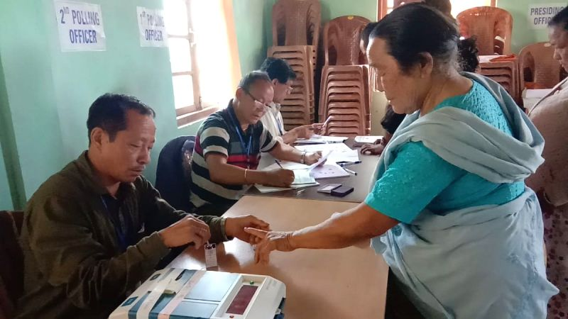 Darjeeling (West Bengal):A polling official administers indelible ink to a voter, at a polling station during the second phase of 2019 Lok Sabha elections in West Bengal's Darjeeling, on April 18, 2019. (Photo: IANS/PIB)