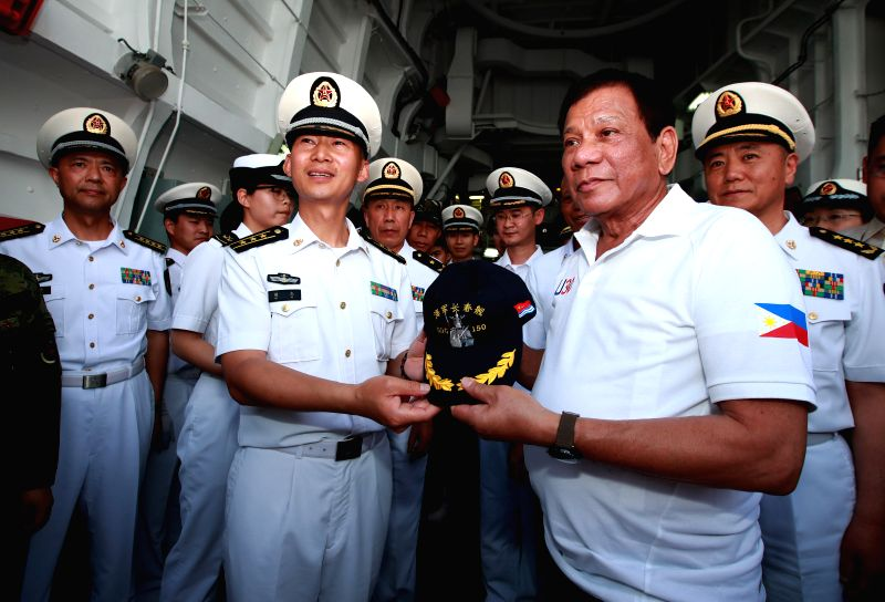 DAVAO CITY, May 1, 2017 - Philippine President Rodrigo Duterte (R, front) receives a hat from Hu Jie (L, front), captain of China's missile destroyer Changchun, in Davao City, the Philippines, May 1, ...