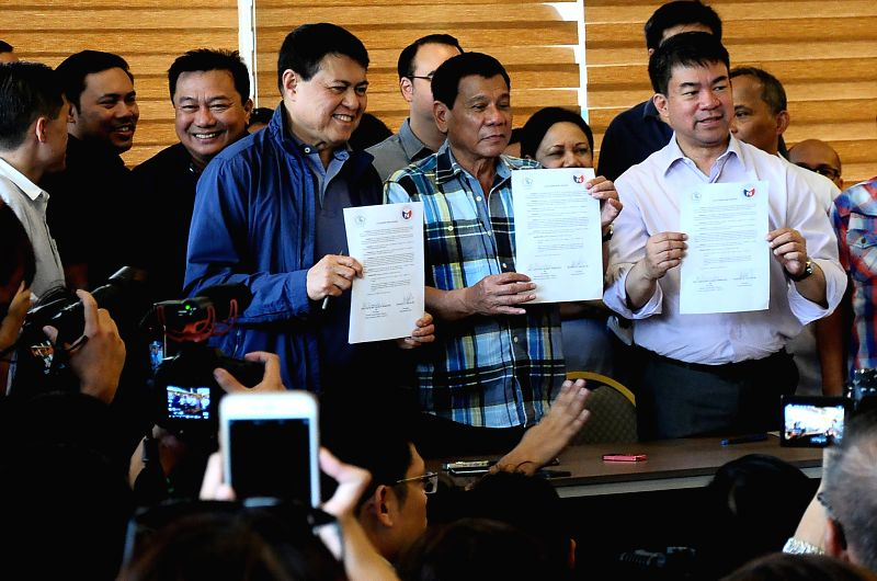 DAVAO PROVINCE, May 16, 2016 - Presumptive Philippine president-elect Rodrigo Duterte poses for photos with members of his political party during a press conference in Davao Province, the ...