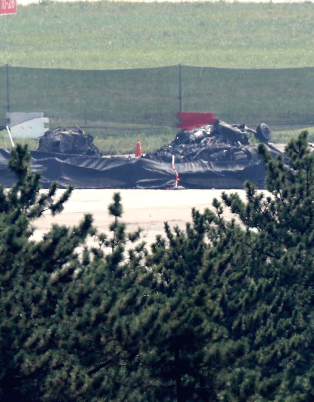 Debris from a Marine Corps helicopter crash remain on the runway of a military airport in Pohang, 370 kilometers southeast of Seoul, on July 18, 2018, a day after the deadly accident. Five of ...
