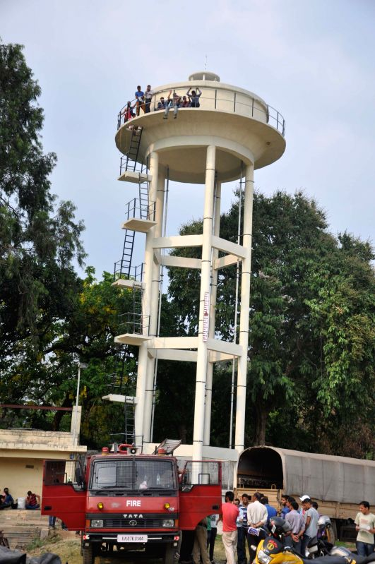 People climb-up on a water tank to press for their demands in Dehradun on June 19, 2015.