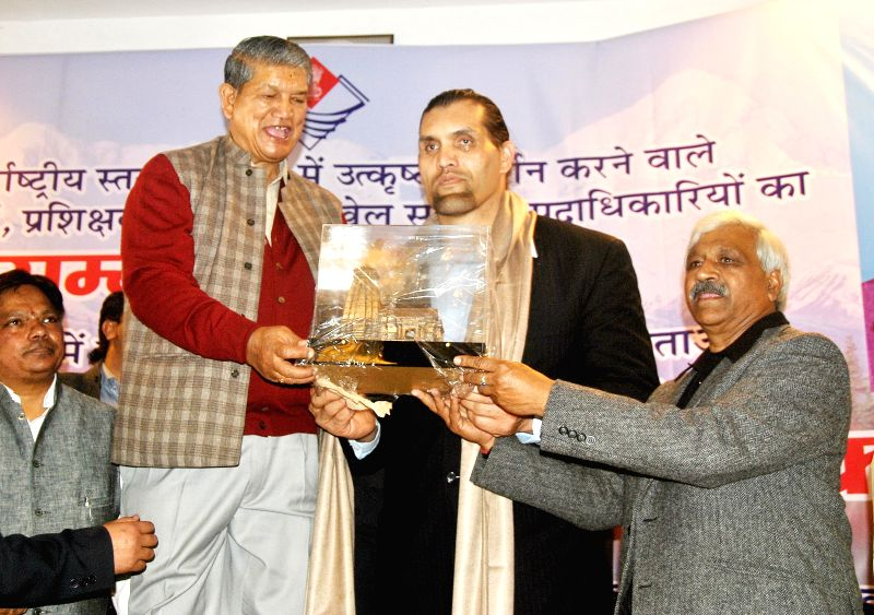 Uttarakhand Chief minister Harish Rawat and Uttarakhand sports minister Dinesh Agarwal presents a memento to the Former WWE World Heavyweight Champion The Great Khali during a felicitation ... - Harish Rawat