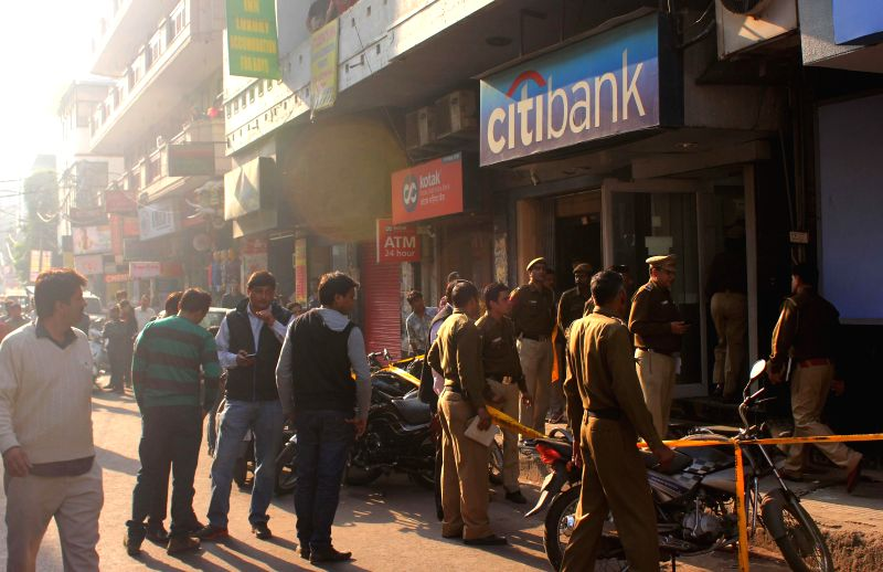 Delhi Police personnel investigating after robbers looted a cash van outside Citi Bank`s ATM in Kamla Nagar area in Delhi on Nov. 29, 2014.
