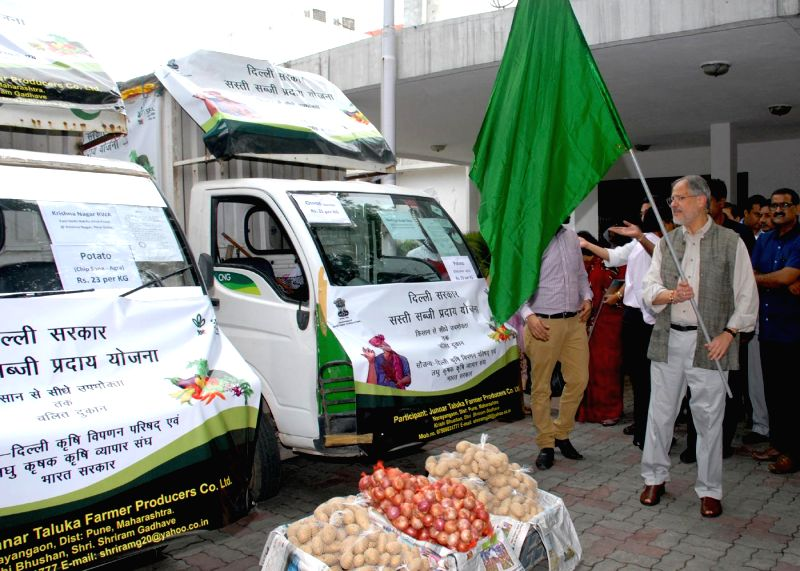 Delhi Lt Governor Najeeb Jung flags-off a fleet of mobile vans which will deliver onions and potatoes to the end users at reasonable rates in New Delhi on Aug 11, 2014.