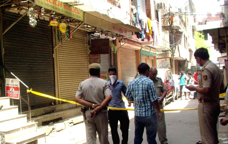 Delhi Police personnel cordon off the area where body of a foreign national was found in Bhogal of New Delhi on April 27, 2014.