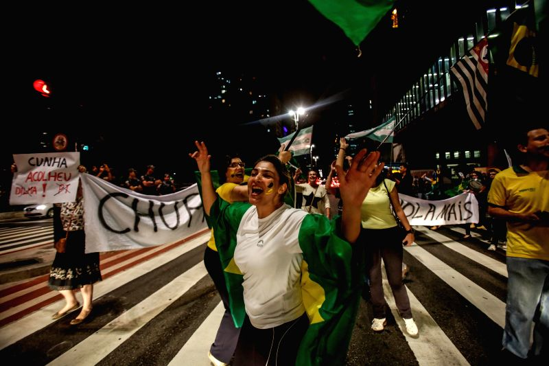 Demonstrators celebrate the announcement of President of the Chamber of Deputies Eduardo Cunha to authorize the opening of impeachment against Brazilian President ...