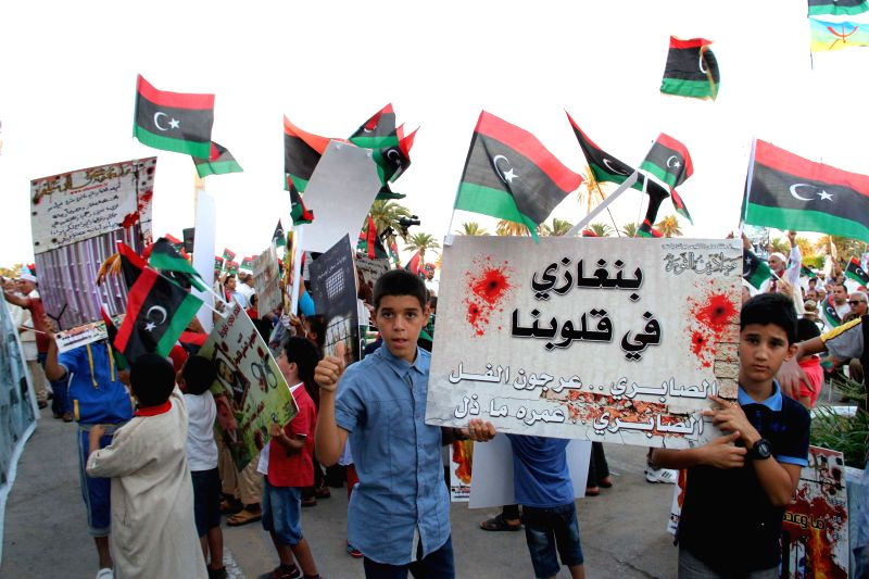 Demonstrators wave banners and hold slogans during a demonstration on the Martyrs Square in Tripoli, Libya, on Aug. 7, 2015. Libyans on Friday held a protest against ...