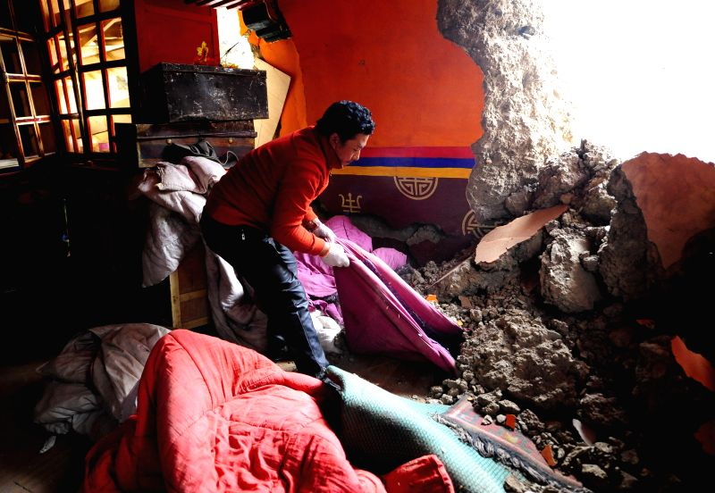 DENGQEN, May 13, 2016 - A villager collects stuff in a damaged house in Guodong Village, Kata Township of Qamdo City, southwest China's Tibet Autonomous Region, May 13, 2016. A 5.5-magnitude ...