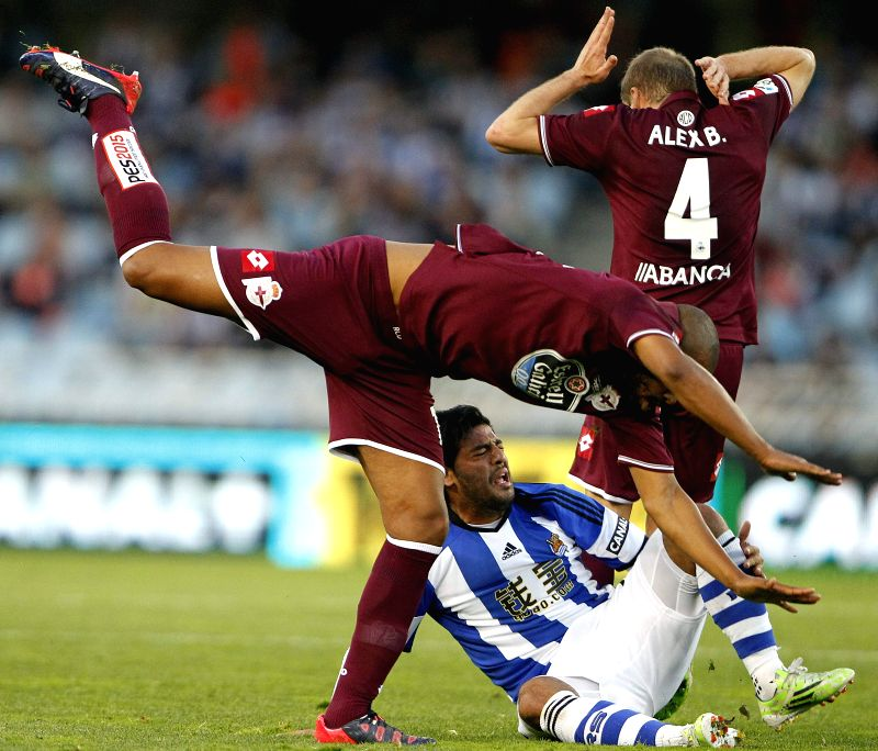 Deportivo La Coruna's Brazilian defender Sidnei Rechel da Silva (L) falls next to Mexican striker Carlos Alberto Vela (C) of Real Sociedad during their Primera Division soccer match played at Anoeta ...