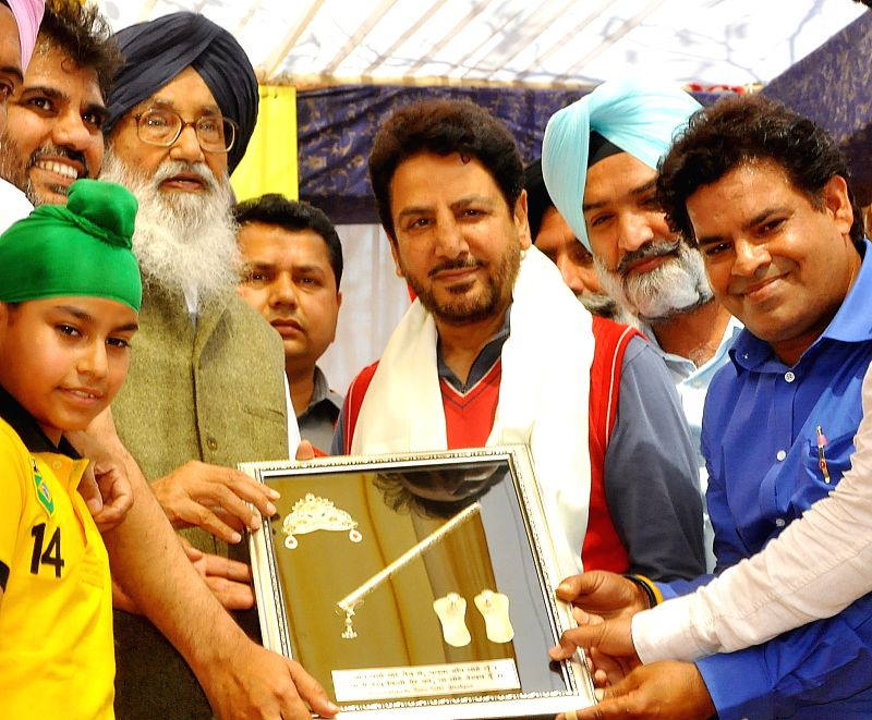 Dera Bassi: Punjab Chief Minister Parkash Singh Badal felicitates renowned singer Gurdas Mann at Government College, Dera Bassi in Mohali district of Punjab on March 24, 2015. - Parkash Singh Badal