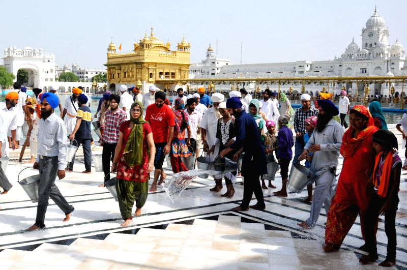 Devotees busy cleaning the Golden Temple in Amritsar on July 13, 2014.