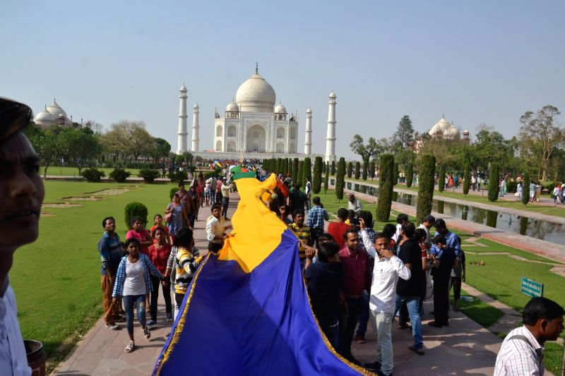Devotees carry a 1,111-feet long multi-color chadar - shawl to be offered at the graves of Mughal emperor Shah Jahan and empress Mumtaz Mahal, during Shah Jahan's Urs (birth anniversary) ...