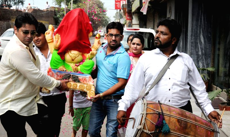 Devotees carry an idol of lord Ganesh during Ganesh festival in Amritsar on Aug 29, 2014.