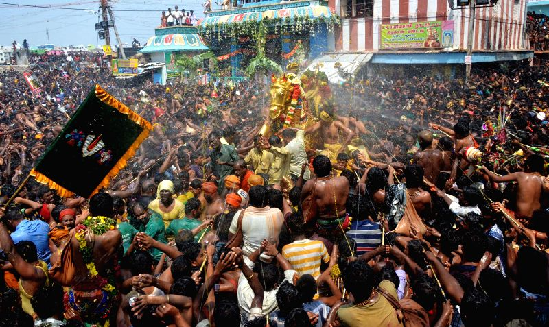 Devotees carry the idol of Lord Kallazhagar for holy bath in the Vaigai river on the last day of Chithrai festival in Madurai on May 14, 2014.