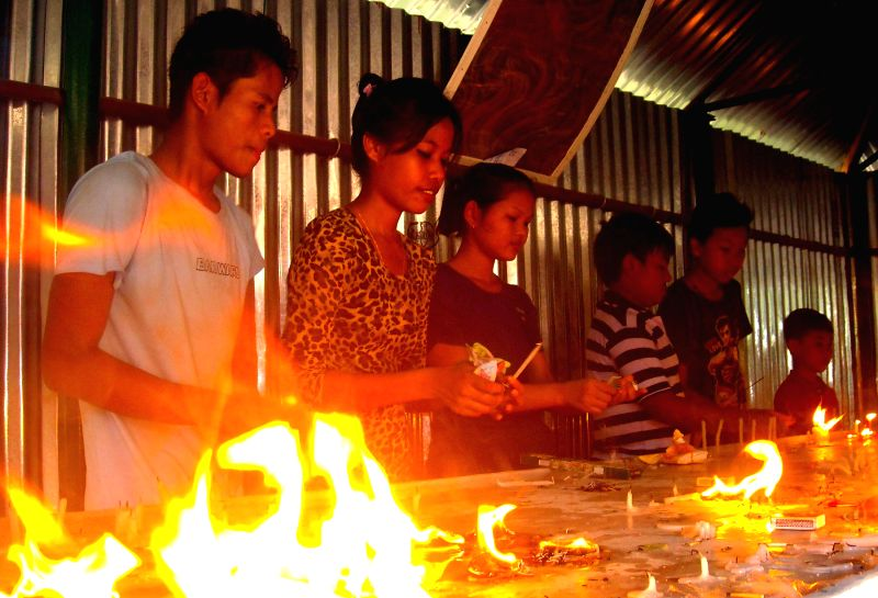 Devotees light candles in a monastery on 2558th birth anniversary of Lord Buddha in Agartala on May 14, 2014. Buddha Purnima is the most sacred day in the Buddhist calendar and celebrated on the ...