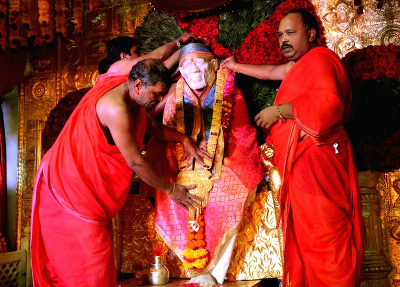 "Devotees offer a 1.5 kilogram gold necklace to Sai Baba on occasion of ""Guru Purnima"" festival at a temple in Nagpur on July 27, 2018."