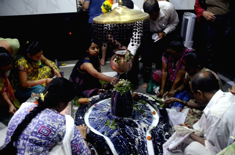 Devotees offer prayers at a Shiva temple during the holy month of `Sawan` in Mumbai on July 28, 2014.