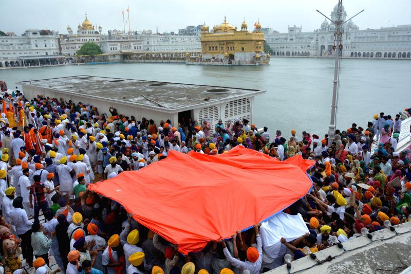 Devotees participate in the Parkash Utsav of Sri Guru Granth Sahib (410th anniversary of installation of the Guru Granth Sahib) at the Golden temple in Amritsar on Sept 1, 2014.