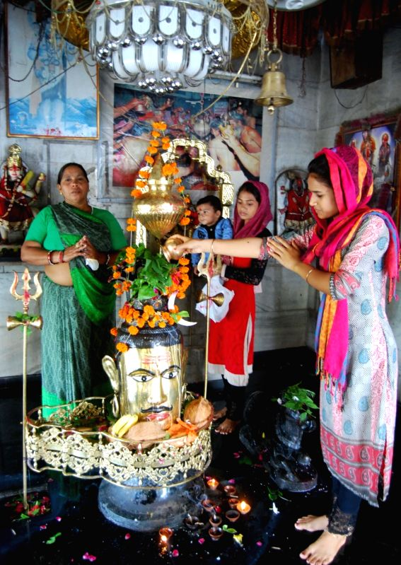 Devotees perform puja on the first monday of Shravan month at a Temple in Bhopal on July 25, 2016.