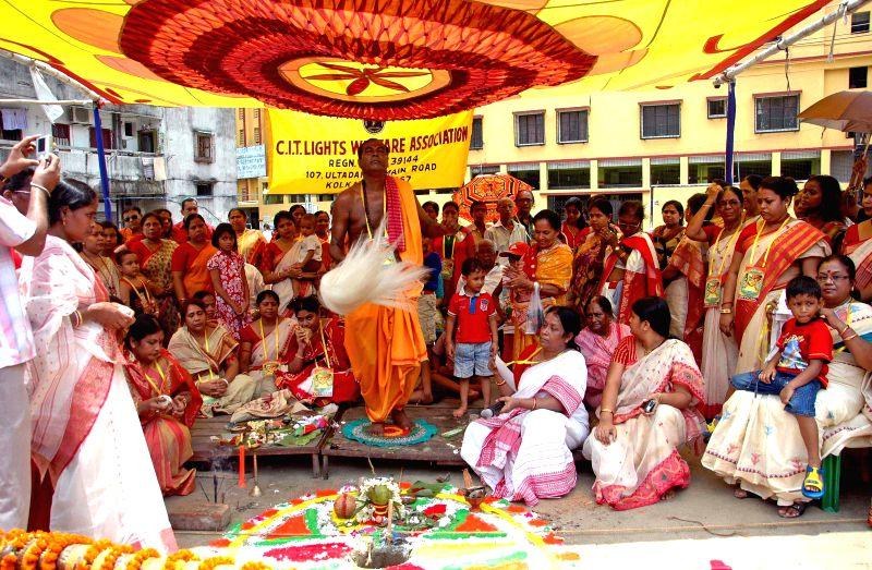 Devotees perform rituals during `Khuti Puja` at Ultadanga in Kolkata on July 6, 2014.