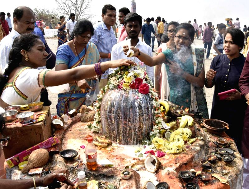 Devotees pour water and milk over the Shiv Linga as they perform rituals on the occasion of Maha Shivaratri at Keesaragutta temple in Medchal-Malkajgiri district in Telangana on Feb 13, ...