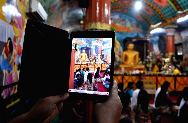 Devotees visit a monastery on 2558th birth anniversary of Lord Buddha in Kolkata on May 14, 2014. Buddha Purnima is the most sacred day in the Buddhist calendar and celebrated on the full-moon day of