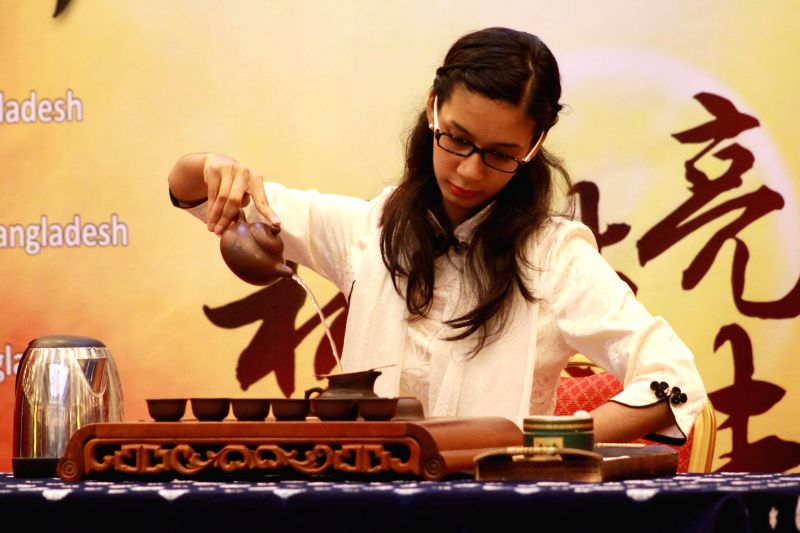 "DHAKA, April 23, 2017 - A contestant shows her Chinese traditional tea making skills during the ""Chinese Bridge"" Chinese proficiency competition for foreign college students in Dhaka, ..."