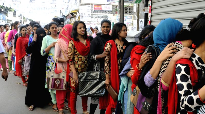 Bangladeshi people queue in a line during the Bangladesh's city corporation and municipal polls in Dhaka, Bangladesh, April 28, 2015. Voting began in Bangladesh's ...
