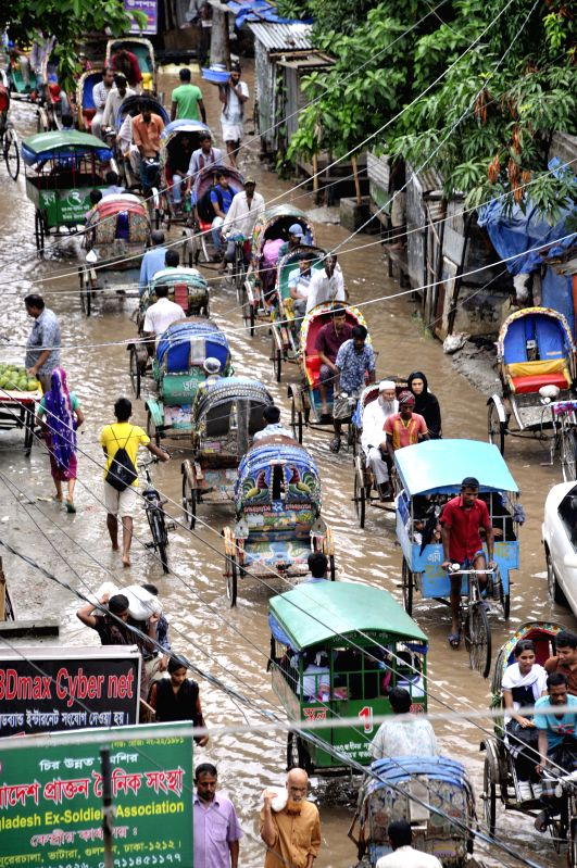 Rickshaw pullers carry passengers on a flooded street after a rainfall in Dhaka, Bangladesh, Aug. 14, 2014.