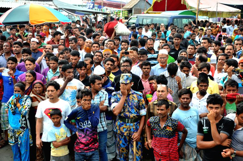 People wait for bodies of victims after a ferry accident on the Padma River in central Bangladesh's Munshiganj district Aug. 6, 2014. The death toll of Monday's ferry .