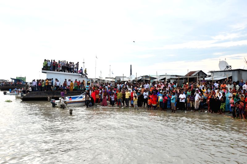 People watch the rescue operations after a ferry accident on the Padma River in central Bangladesh's Munshiganj district Aug. 6, 2014. The death toll of Monday's ferry