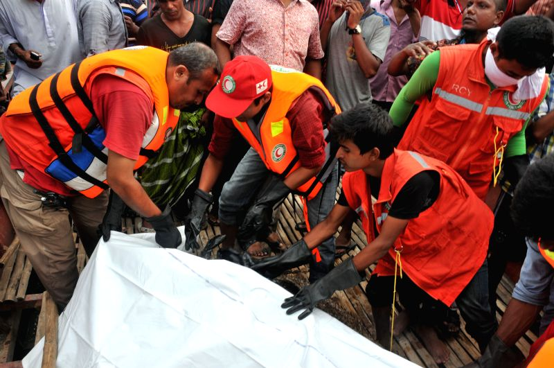 Rescuers cover a body after a ferry accident on the Padma River in central Bangladesh's Munshiganj district Aug. 6, 2014. The death toll of Monday's ferry capsizal has