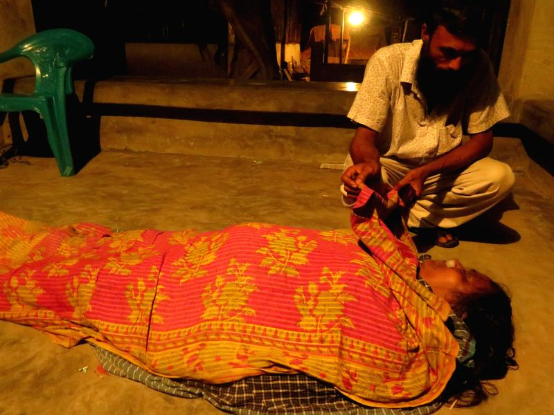 DHAKA (BANGLADESH), Aug. 4, 2014 A man identifies the body of a victim at the site of a ferry accident in the Munshiganj district, some 27 km south of capital Dhaka, Bangladesh, Aug. 4, ..