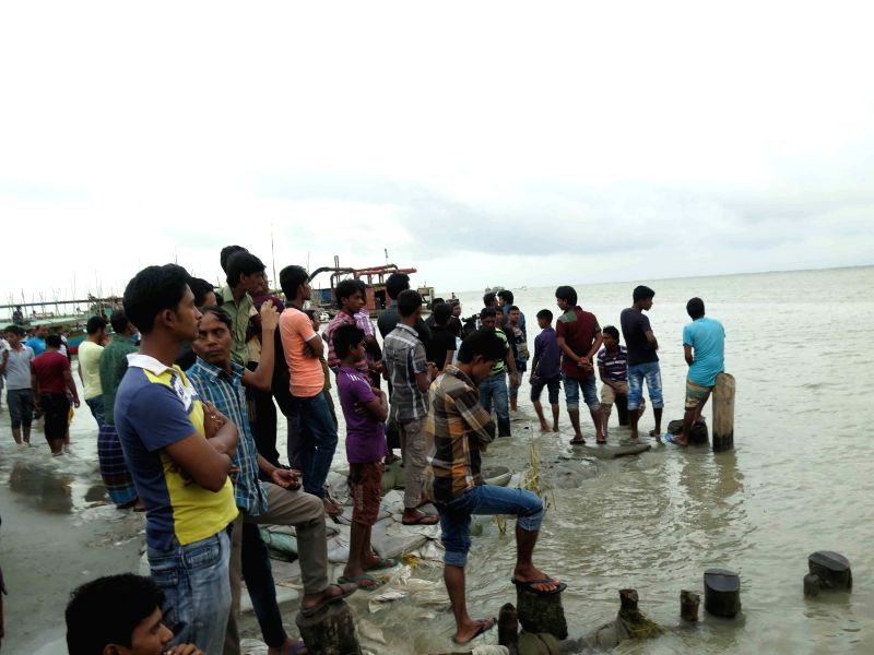 DHAKA (BANGLADESH), Aug. 4, 2014 People watch the search operation at the site of a ferry accident in the Munshiganj district, some 27 km south of capital Dhaka, Bangladesh, Aug. 4, 2014.