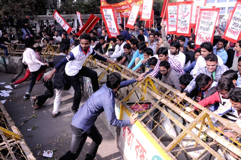Protesters try to remove police barricade during a protest against the hike in gas and electricity prices in Dhaka, capital of Bangladesh, on Dec. 18, 2014. ...