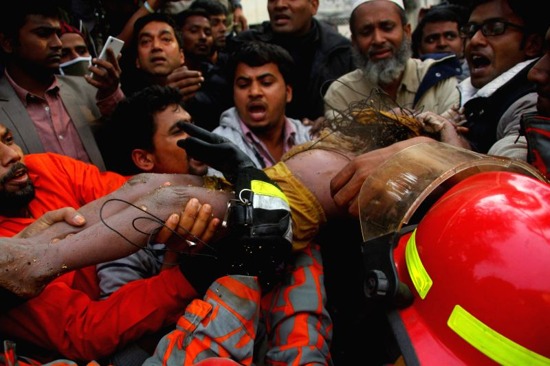 People carry a boy in Dhaka, Bangladesh, Dec. 27, 2014. The boy was recovered from a deep well shaft in the Shahjahanpur area of Dhaka despite authorities' repeated ..